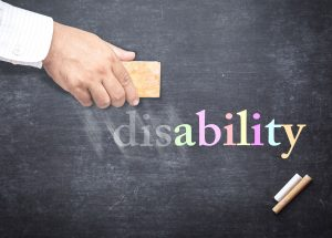 A hand erasing the dis from the word disability, which is written on a chalkboard