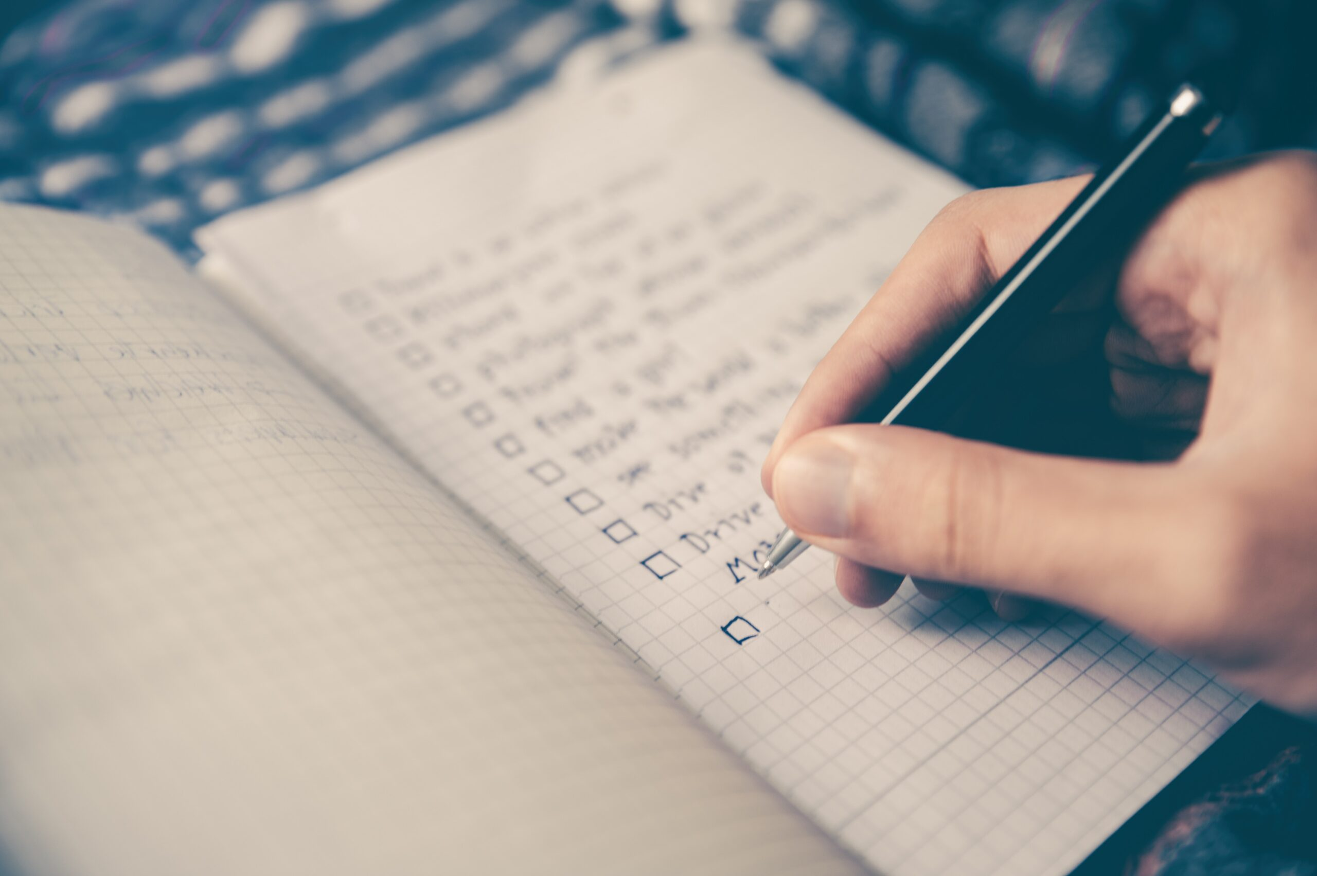 Person creating a list of necessary components with a pen on paper.