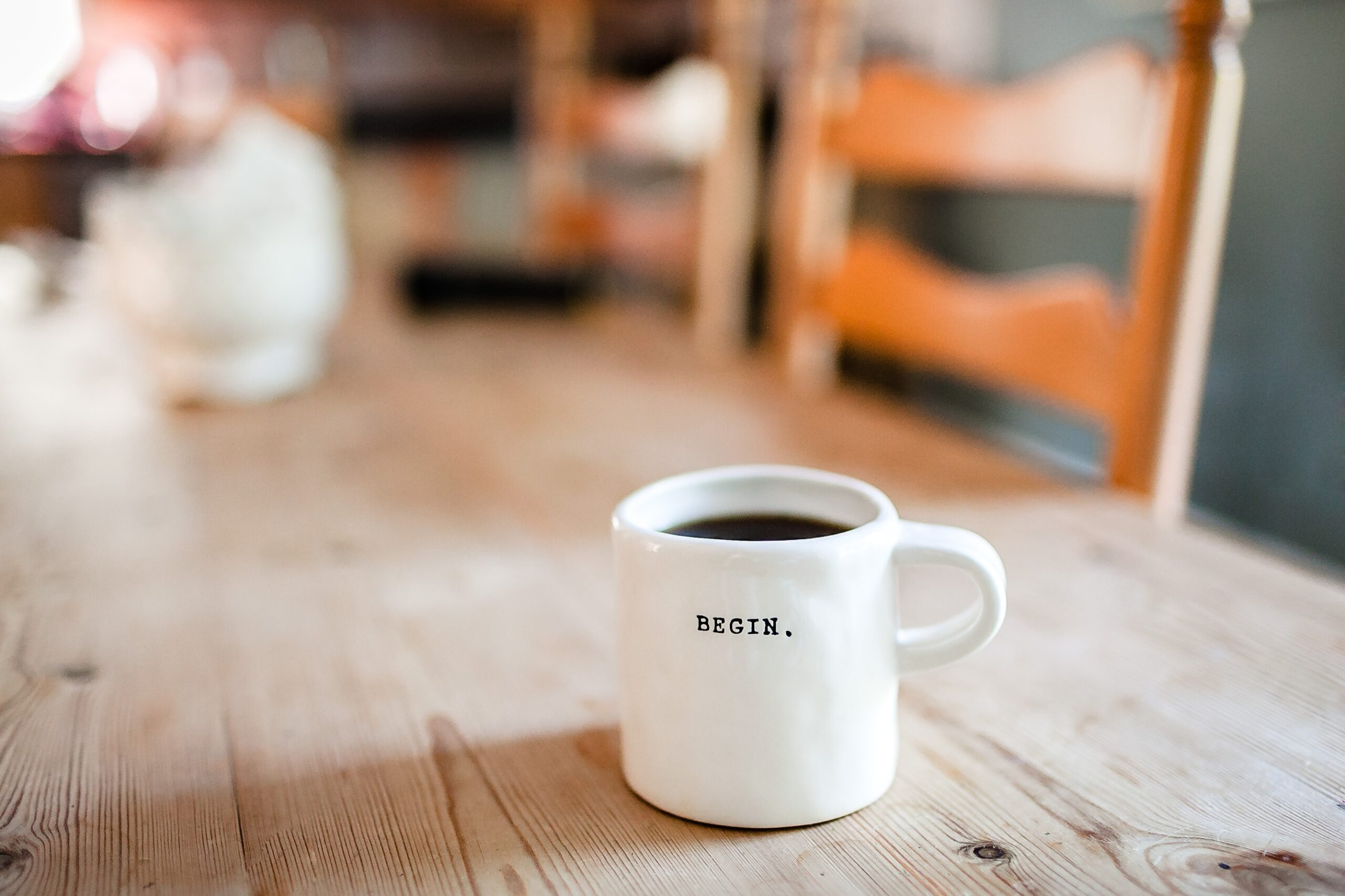 A full coffee cup basking in beautiful natural light from a window, with the word Begin