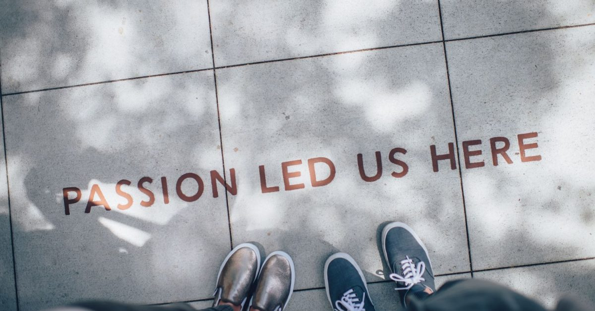 two people standing on gray tile paving that reads passion led us here