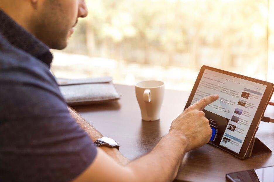 Man Scrolling Through Social Media on an iPad