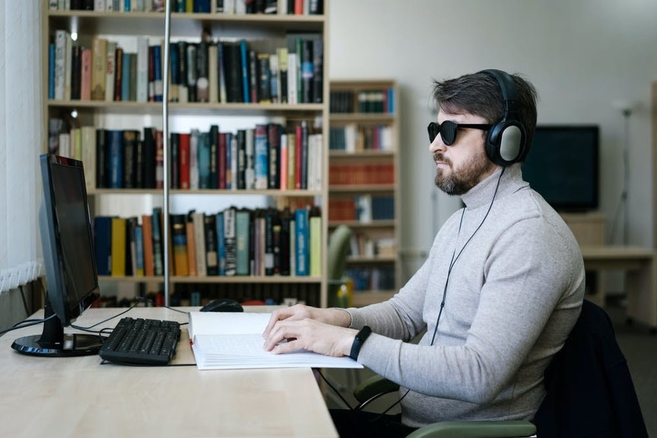 A man wearing headphones and sunglasses sitting at a desk with a computer