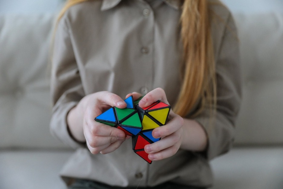 Girl indoors playing with rubiks cube