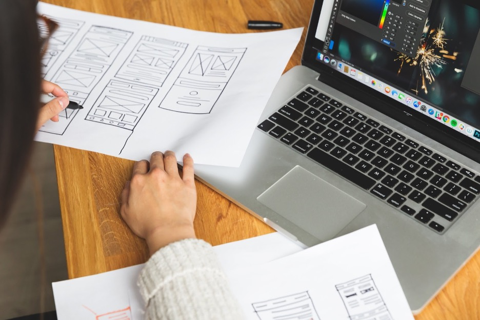 A person working on a computer and sketching wireframes