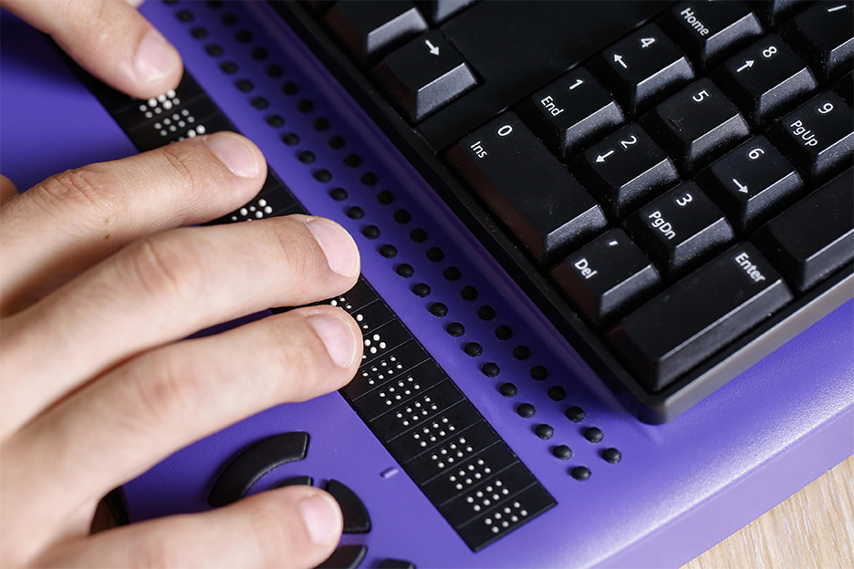 Person using braille keyboard